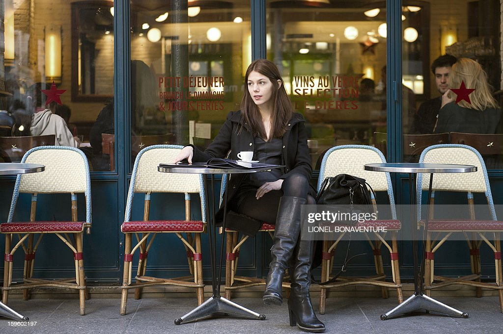 LACUT - Romanian model Ioana Timoce sits at a cafe terrace with her personal book on January 16, 2013 in Paris. Ioana Timoce works with the agency H Model Management for the fashion week in Paris. AFP PHOTO / LIONEL BONAVENTURE