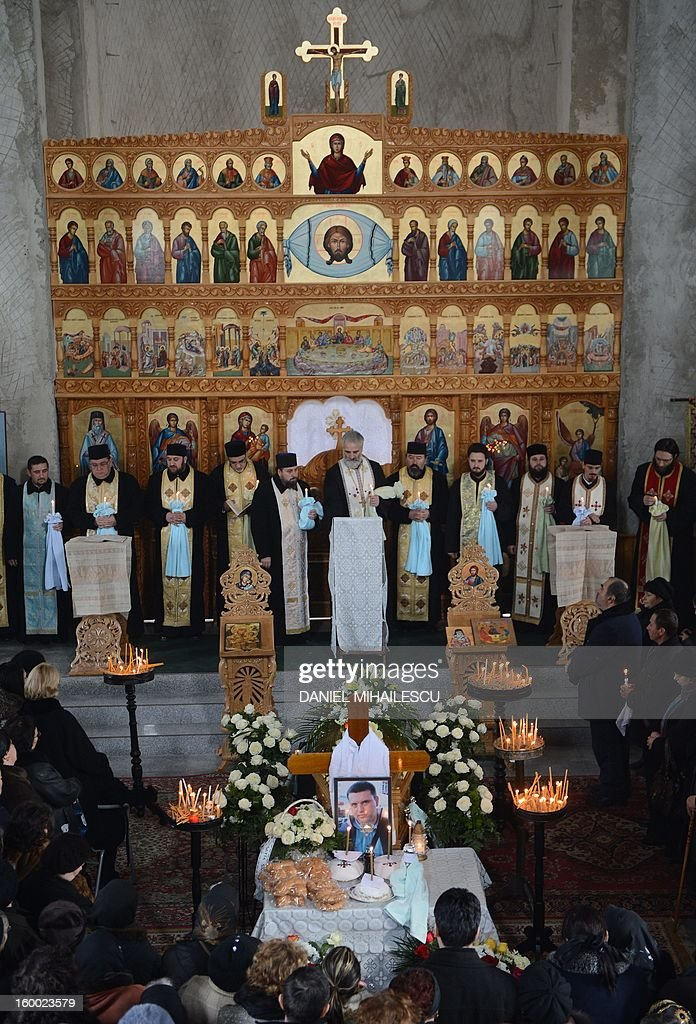 Romanian orthodox priests celebrate the funeral service for Tiberiu Ionut Costache, 36, one of the two Romanian victims who were killed during the Algerian hostage crisis, at the Orthodox church in Barcanesti village (50km north of Bucharest), January 24, 2012. Three other Romanians escaped the audacious attack by Islamist militants on a gas plant in the Algerian desert.