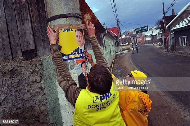 Romanian party activists fix an National Liberal Party electoral poster in Hoghiz village on November 25 2008 Romanians are called to ballots next...