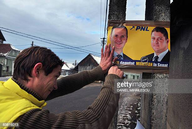 Romanian party activists fix an National Liberal Party's electoral poster in Hoghiz village on November 25 2008 Romanians are called to ballots next...