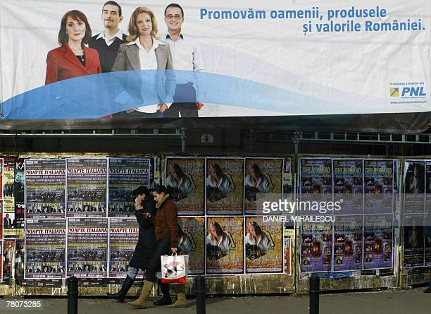 Romanian people walk under a National Liberal Party banner reading 'We promote the people and the values of Romania' and showing portraits of PNL...