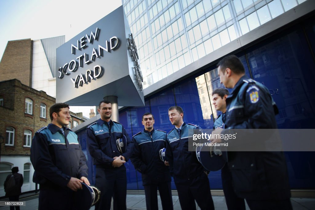 Romanian police officers stand outside Scotland Yard on October 24 2013 in London England Eight Romanian and three Polish officers are to work in...
