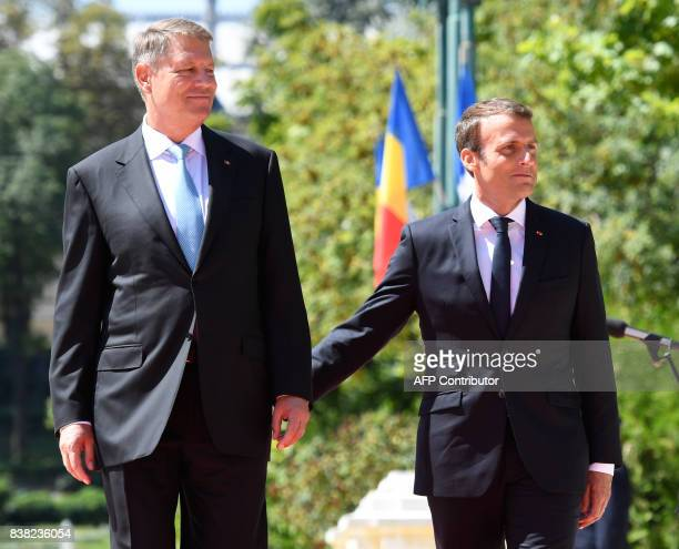 Romanian President Klaus Iohannis and French President Emmanuel Macron review the guards of honour on August 24 2017 at Cotroceni Palace in Bucharest...