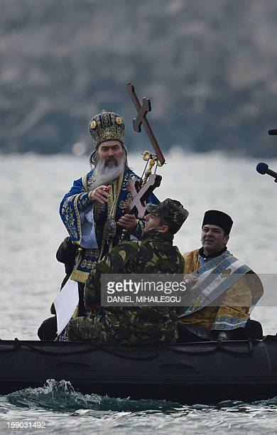 A Romanian priest throws a wooden cross in the Black Sea during an epiphany religious service in Constanta city on January 6 2013 Thousands romanian...