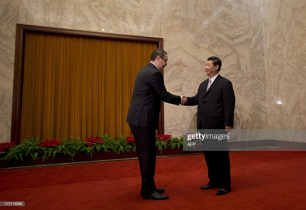 Romanian Prime Minister Victor-Viorel Ponta (L) is greeted by Chinese President Xi Jinping upon arrival for a meeting at the Great Hall of the People in Beijing on July 2, 2013. Ponta, on an official tour of several Asian countries, is seeking to attract Chinese investments in Romania. AFP PHOTO / Andy Wong / POOL