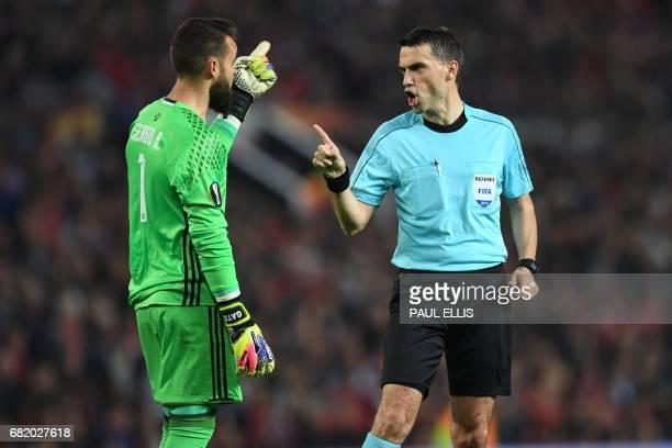 Romanian referee Ovidiu Hategan has words with Celta Vigo's Spanish goalkeeper Sergio Alvarez during the UEFA Europa League semifinal secondleg...