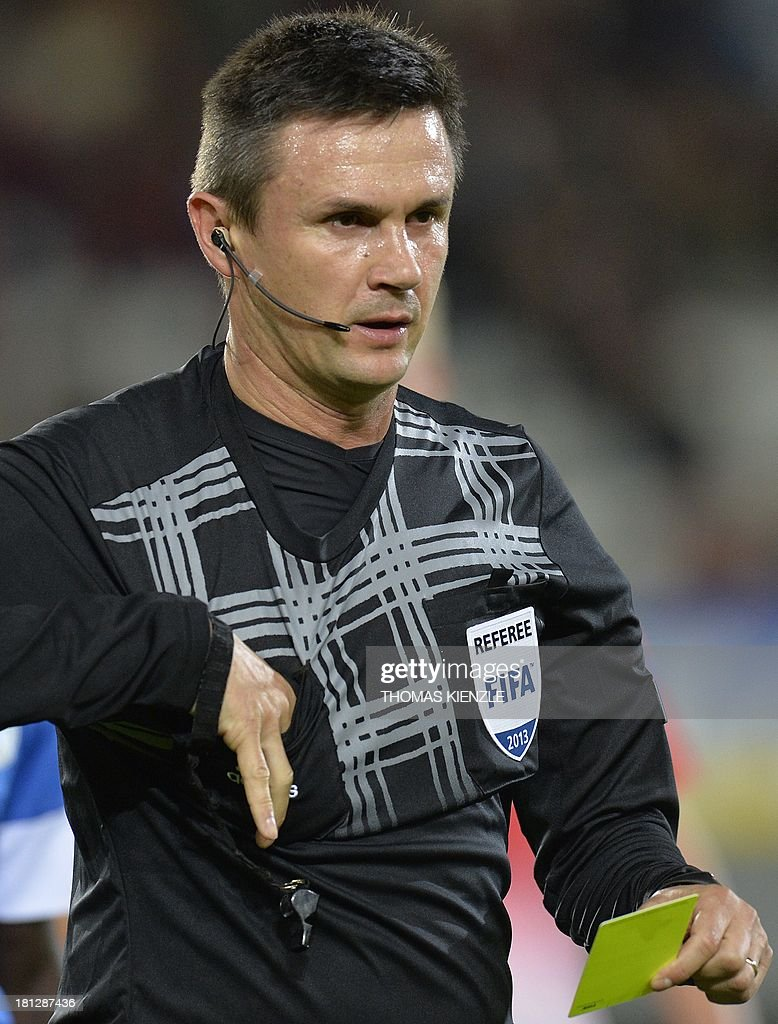 Romanian referee Pavel Cristian Balaj holds the yellow card during Europa league football match between SC Freiburg vs FC Slovan Liberec in Freiburg on September 19, 2013.