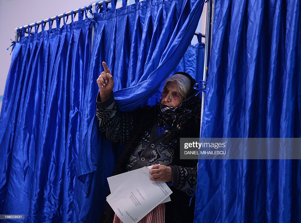 A Romanian Roma woman exits a vote cabin at a polling station in Pantelimon village, near Bucharest, on December 9, 2012 as Romanians head to the polls to elect a new parliament. The centre-left ruling coalition of Prime Minister Victor Ponta is on course for a large victory, an outcome that would create a bitter cohabitation with centre-right President Traian Basescu.