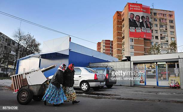 Romanian Roma women pull a cart laden with debris used for firewood as they walk past a giant electoral poster hanging on a building showing...