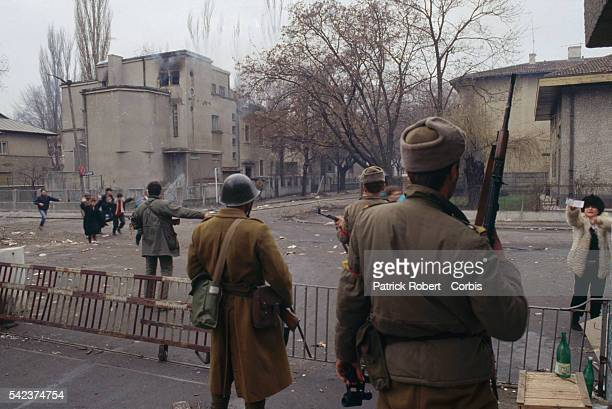 Romanian soldiers guard citizens crossing a street near a burning building during the December 1989 uprising which marked the end of Communist...
