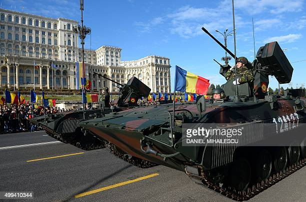 Romanian soldiers in tanks parade past the Palace of the Parliament during a military parade in Bucharest to celebrate the National Day of Romania on...