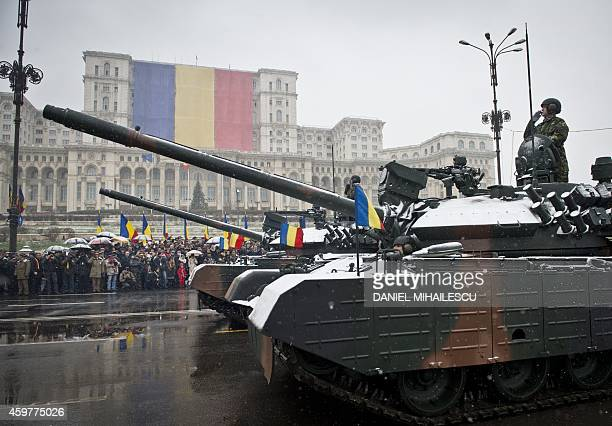 Romanian soldiers on tanks parade in front of the Parliament building in Bucharest during festivities to celebrate the National Day of Romania on...