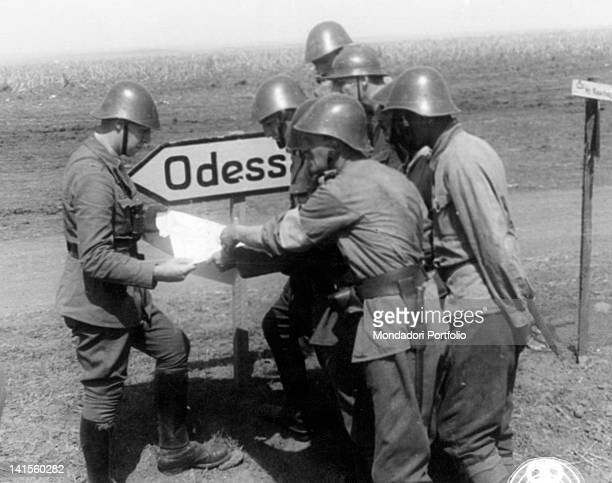 Romanian soldiers studying a map next to a road sign that shows the way to Odessa Ukraine August 1941