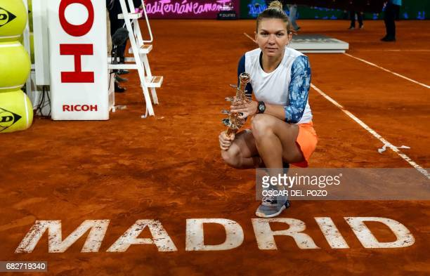 Romanian tennis player Simona Halep poses with her trophy as she celebrates her victory over French tennis player Kristina Mladenovic after the WTA...