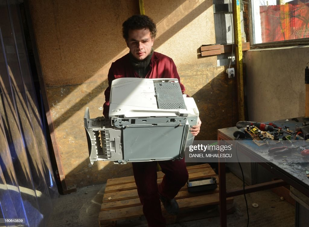 A Romanian worker carries a broken printer to be dismantled at 'Ateliere fara frontiere' (Workshops without borders) recycling factory in Bucharest February 1, 2013. 'Workshops Without Borders' is inspired by Ateliers Sans Frontieres, a nonprofit association whose mission is socio-professional integration of people in need through a shop which proposes an economic activity and solidarity: recycling and reconditioning computers collected from companies and institutions responsible.