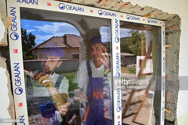 Romanian workers of Roma origin install window frames made at a local doubleglazing workshop in a home on September 2 2010 in the village of...