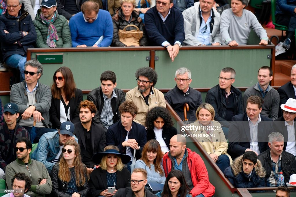 Romanian-born French film director Radu Mihaileanu (2nd row from top, C) and French actress Marilou Berry (bottom row, wearing hat) attend the men's fourth round match between Japan's Kei Nishikori and France's Richard Gasquet at the Roland Garros 2016 French Tennis Open in Paris on May 29, 2016. / AFP / MARTIN