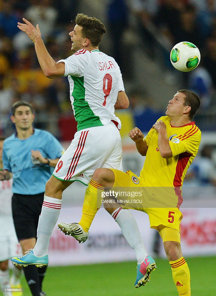 Romania's Alexandru Bourceanu (R) vies for the ball with Hungary's player Adam Szalai during the FIFA World Cup 2014 group D qualifying football match Romania vs Hungary on September 6, 2013 in Bucharest, Romania. Romania won 3-0.