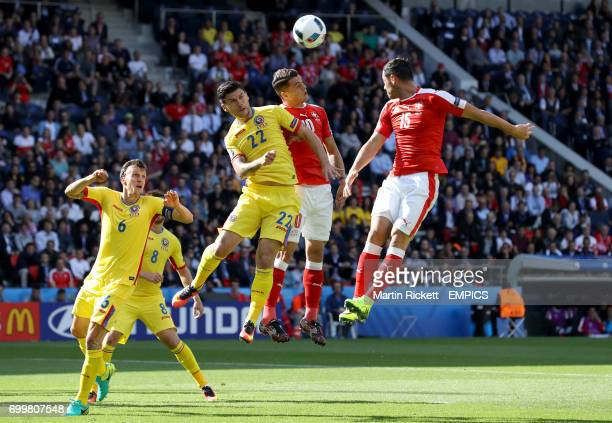 Romania's Cristian Sapunaru battle for the ball in the air with Switzerland's Granit Xhaka and Blerim Dzemaili