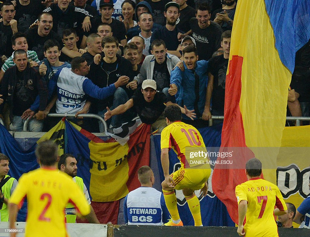 Romania's Cristian Tanase (C) celebrates with the fans after he scored the 3-0 during the FIFA World Cup 2014 group D qualifying football match of Romania vs Hungary on September 6, 2013 in Bucharest, Romania. Romania won the match 3-0.