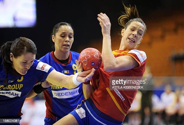 Romania's Cristina Neagu and Aurelia Bradeanu push Spain's Begona Fernandez during the 2012 EHF European Women's Handball Championship Group II match...