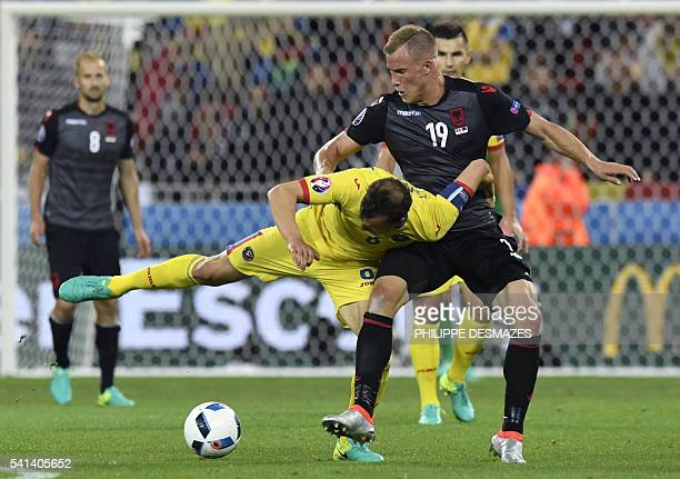TOPSHOT Romania's defender Vlad Chiriches and Albania's forward Bekim Balaj vie for the ball during the Euro 2016 group A football match between...