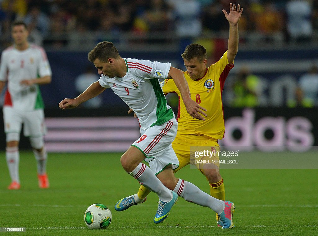 Romania's Doru Pintilii (R) vies for the ball with Hungary's player Adam Szalai during the FIFA World Cup 2014 group D qualifying football match of Romania vs Hungary on September 6, 2013 in Bucharest, Romania. Romania won the match 3-0.