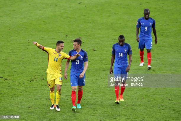 Romania's Florin Andone and France's Laurent Koscielny in conversation at halftime