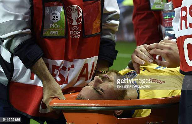 Romania's forward Denis Alibec reacts as he is carried of the pitch on a stretcher after an injury during the Euro 2016 group A football match...