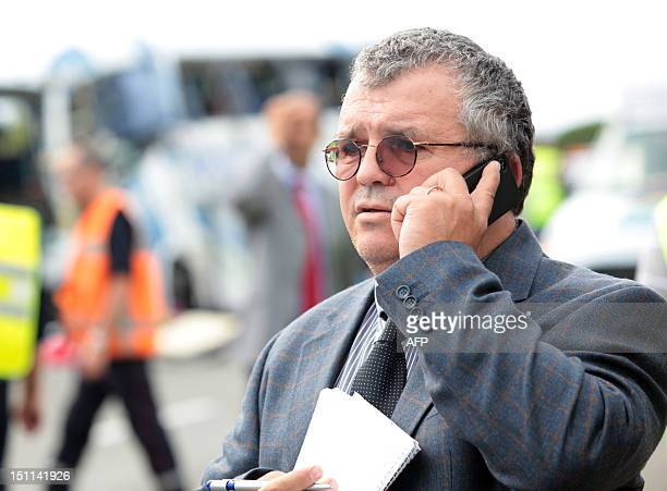 Romania's General Consul in Marseille Ioan Morar talks on a mobile phone on September 2 near the resting area of the southern French city of Vidauban...