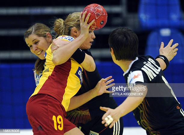 Romania's Iulia Curea vies with Germany's Marlene Zapf and Germany's Anne Müller during the 2012 EHF European Women's Handball Championship Group II...