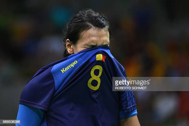Romania's left back Cristina Neagu hides her face in her jersey as she reacts after being defeated at the end of the women's preliminaries Group A...