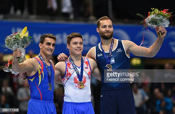 Romanias Marian Dragulescu Russias Nikita Nagornyy and Israels Alexander Shatilov celebrate on the podium after the Mens Floor competition of the...