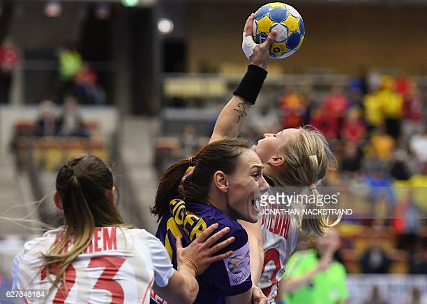 TOPSHOT Romania's Melinda Geiger vies with Norway's Camilla Herrem and Stine Oftedal during the Women's European Handball Championship Group D match...