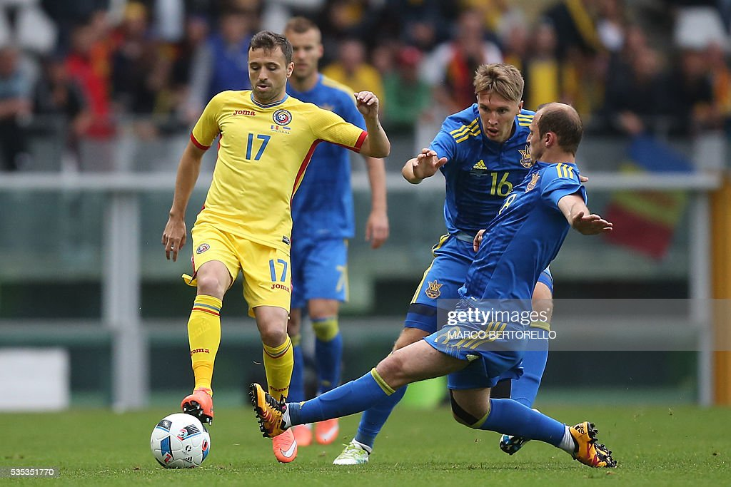 Romania's midfielder Lucian Sanmartean (L) fights for the ball with Ukraine's forward Roman Zozulya and Ukraine's midfielder Serhiy Sydorchuk (C)during the international friendly football match between Romania Vs Ukraine at 'Grande Torino Stadium' in Turin, on May 29, 2016. / AFP / MARCO