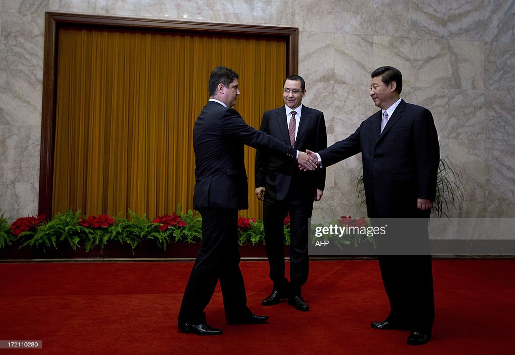 Romania's Prime Minister Victor-Viorel Ponta (C) looks on as Chinese President Xi Jinping shakes hand with a Romanian delegate ahead of a meeting at the Great Hall of the People in Beijing on July 2, 2013. Ponta, on an official tour of several Asian countries, is seeking to attract Chinese investments in Romania. AFP PHOTO / Andy Wong / POOL