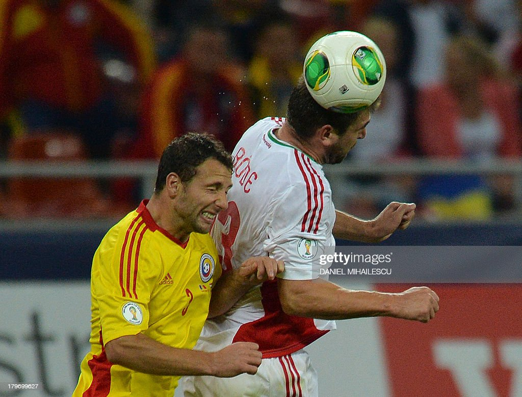 Romania's Razvan Rat (L) heads for the ball with Hungary's player Daniel Bode during the FIFA World Cup 2014 group D qualifying football match of Romania vs Hungary on September 6, 2013 in Bucharest, Romania. Romania won the match 3-0.