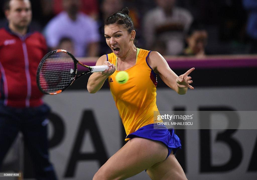Romania's Simona Halep returns the ball to Czech Republic's Petra Kvitova (unseen) during the FedCup tennis match at 'Sala Polivalenta Cluj Napoca' hall in Cluj Napoca city, on February 7, 2016. / AFP / DANIEL MIHAILESCU
