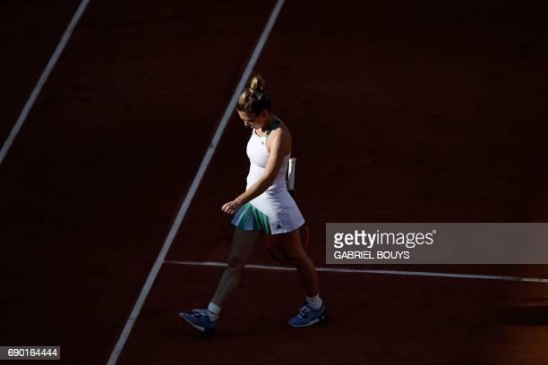 Romania's Simona Halep walks on the court as she plays against Slovakia's Jana Cepelova during their tennis match at the Roland Garros 2017 French...