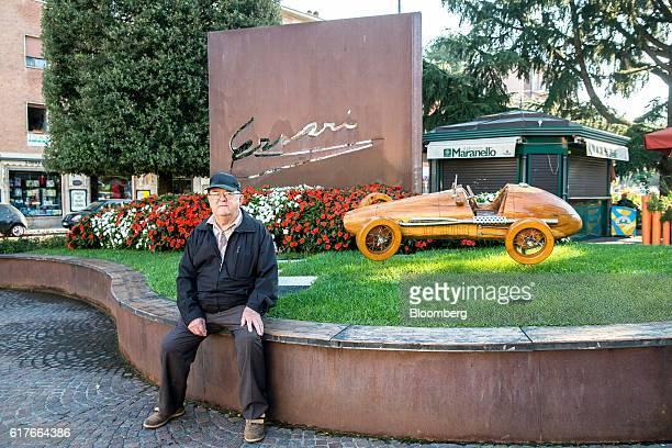 Romano Bonacorsi a retired ceramic worker poses for a photograph beside a wooden replica of a Ferrari SpA automobile after an interview in Maranello...