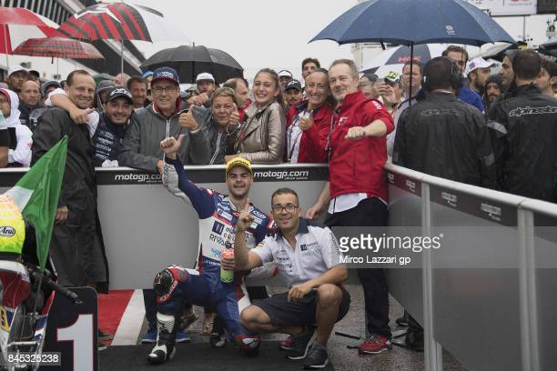 Romano Fenati of Italy and Marinelli Rivacold Snipers Team celebrates the victory under the podium with team at the end of the Moto3 Race during the...