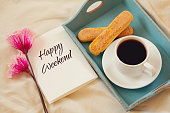 Romantic breakfast in the bed: cookies, hot coffee, flowers and note with the text: HAPPY WEEKEND