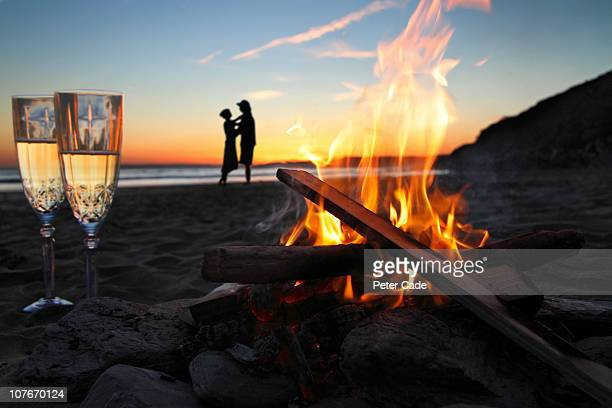 Romantic couple, beach, fire and champagne