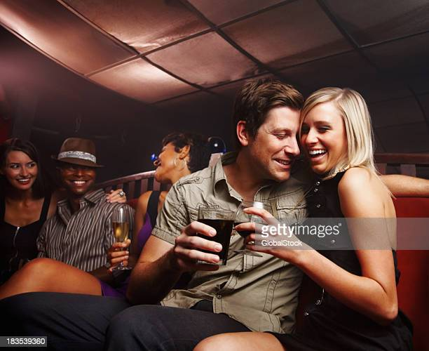 Romantic couple celebrating with friends at a night party