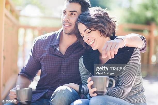Romantic couple drinking coffee in front porch