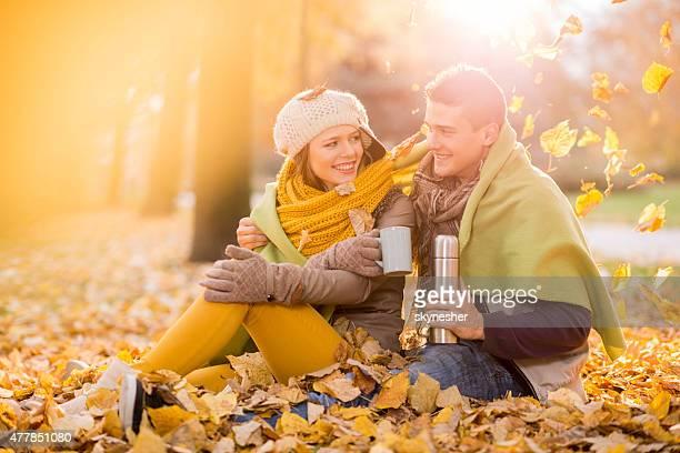 Romantic couple drinking tea and talking in autumn park.