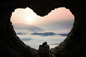 Silhouette of happy couple sitting inside cave shaped heart symbol while enjoying mountain view
