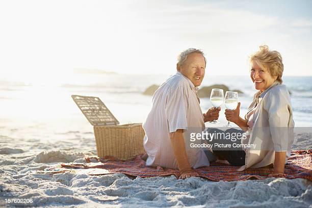 Romantisches Paar Genießen Sie ein Glas Wein, während Sie am Strand