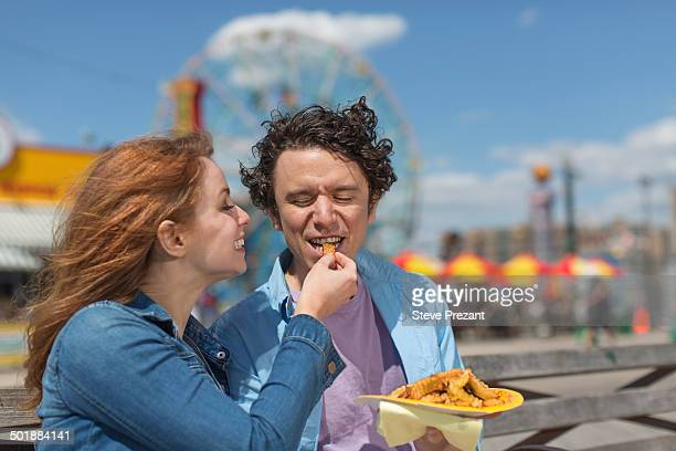 Romantic couple feeding each other chips at amusement park