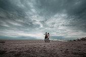 Romantic couple holding hands walking on beach